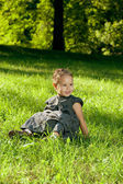 Baby girl is sitting on a green lawn in morning sunlight. — Stock Photo