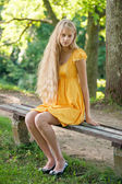 Blond Girl with long hair in yellow dress sitting on a bench — Stock Photo