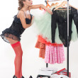 Sexy woman standing in front of a rack of clothes — Stock Photo