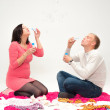 Happy beautiful pregnant woman and her husband blowing soap bubbles — Stock Photo #36406501