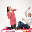 Happy beautiful pregnant woman and her husband blowing soap bubbles — Stock Photo