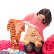 Pregnant woman with teddy bear and children's clothes — Stok fotoğraf