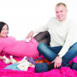 Happy pregnant woman with her husband looking at clothes for their future child — Stock Photo
