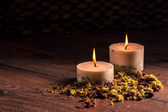 Dry flowers petals and candles — Stock Photo