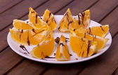 Pieces of oranges on the plate with chocolate — Stock Photo