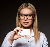 Attractive businesswoman with a blank business card — Stock Photo