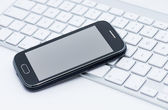 Business smartphone on the keyboard — Stock Photo