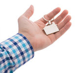 Close-up of hand giving a key ring with house isolated on white — Stok fotoğraf