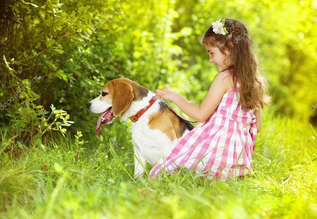可爱的小女孩在玩她的小狗的绿色公园
