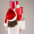 Small girl in santa hat with christmas gift — Stock Photo