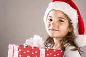 Small girl in santa hat with christmas gift — Foto de Stock