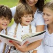 Mother and kids reading a book — Stock Photo