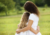 Mother and daughter hugging — Stock Photo