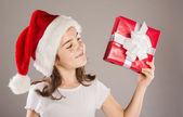 Small girl in santa hat with christmas gift — Foto Stock