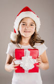 Small girl in santa hat with christmas gift — Stockfoto