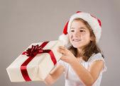 Klein meisje in kerstman hoed met de gift van kerstmis — Stockfoto