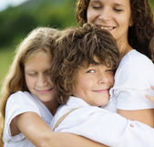 Children and mother hugging — Stock Photo
