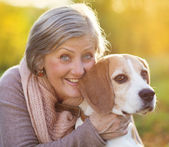 Active senior woman hugs dog — Stock fotografie