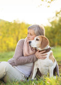 Active senior woman hugs dog — Stock Photo