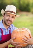 Gardener with huge pumpkin — Stock Photo