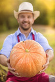 Gardener with huge pumpkin — Stock Photo