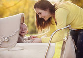 Baby in vintage pram with his mother — Stock Photo