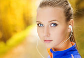 Sporty woman runner listens to music in nature — Stock Photo
