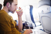 Man in the aircraft is drinking water — Stock Photo