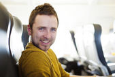 Happy man in the aircraft is flying abroad — Stock Photo