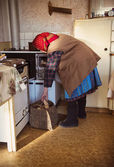 Old woman in the kitchen — Stock Photo