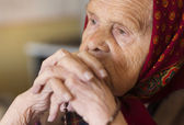 Old woman praying — Stock Photo