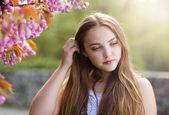Girl among the blooming trees — Stock Photo
