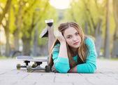 Girl with skateboard lying in alley — Stock fotografie