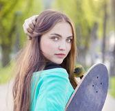 Menina com skate no parque — Fotografia Stock