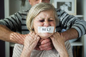Man strangles woman with tape on her mouth — Stock Photo