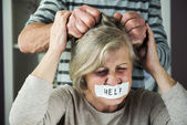 Man abusing woman with tape on her mouth — Stock Photo