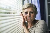 Woman looking through window — Stock Photo