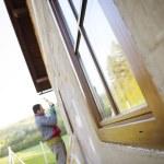 Man applying foam to insulate window — Stock Photo #46150577