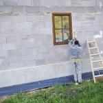 Man applying foam to insulate window — Stock Photo #46150675