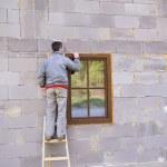 Man applying foam to insulate window — Stock Photo #46150703