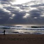 Man goes to sea on dark beach — Stock Photo