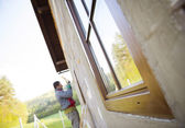 Man applying foam to insulate window — Stock Photo