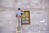 Man applying foam to insulate window — Foto de Stock