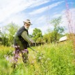Farmer using scythe to mow grass — Stock Photo #46524711