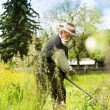 Farmer using scythe to mow grass — Stock Photo #46524735