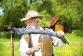 Farmer sharpening his scythe — Stock Photo
