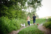 Couple walking with dogs — Stock Photo