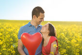 Couple with heart shaped baloon — Stock Photo
