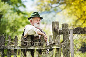 Farmer standing  by the lath fence — Stock Photo