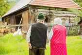 Couple standing by farmhouse — Stockfoto